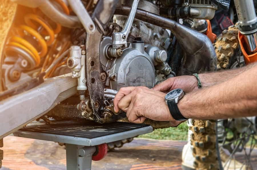 Photo of man changing oil on 4 stroke dirt bike engine.
