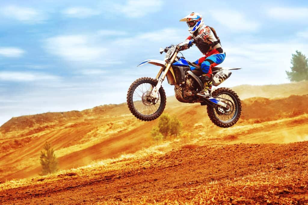 Dirt bike speeding across the landscape. Rider loving it.